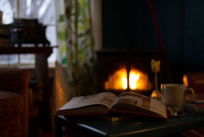 Open book open on table next to coffee cup in front of fireplace.jpg