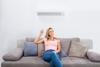 Woman Operating Air Conditioner With Remote Control.jpg