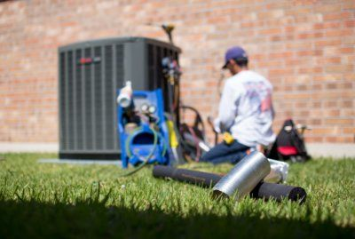HVAC technician working on air conditioning unit next to red brick building home.jpg