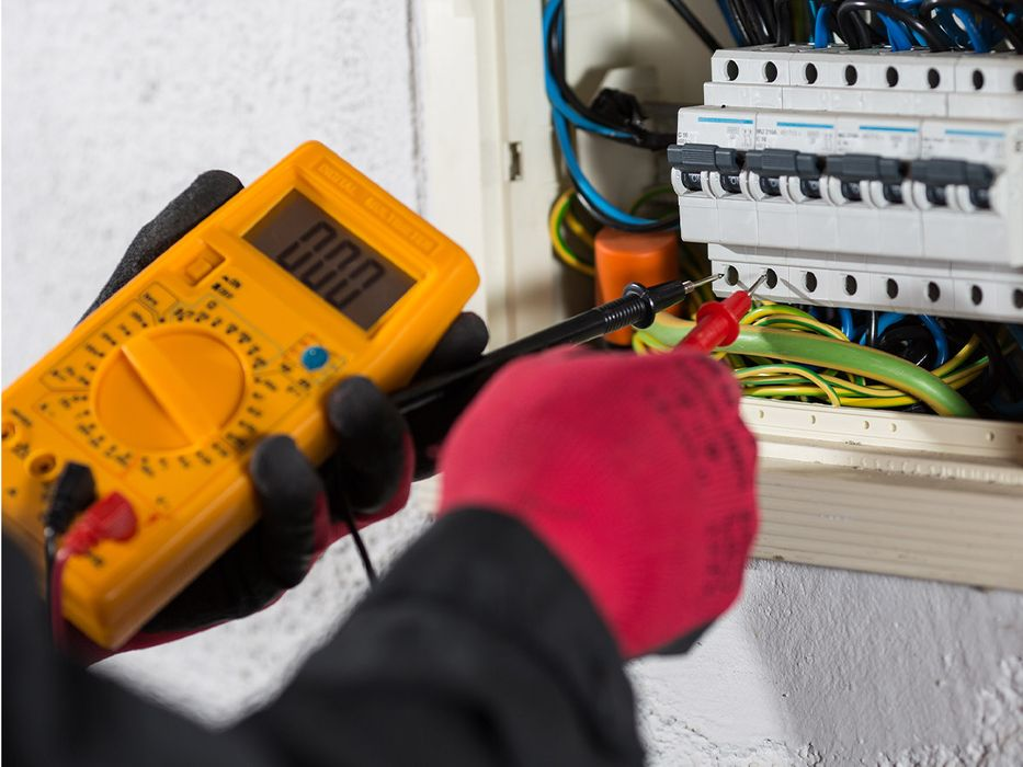 electrician performing test on an electrical panel