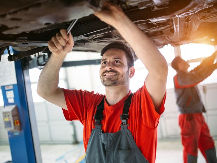 Car mechanic changing motor oil in automotive engine and maintenance repair service station.