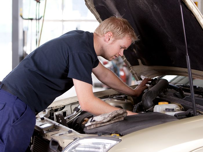 A young mechanic under the hood of a car performing an inspection.