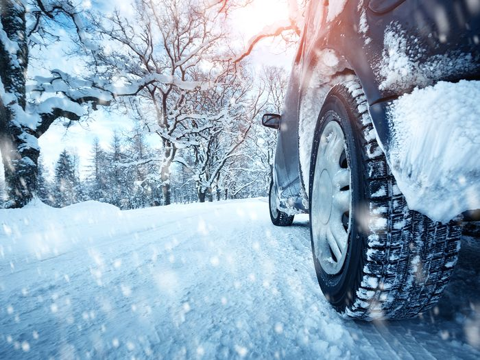 Car tires on winter road that is packed with snow.