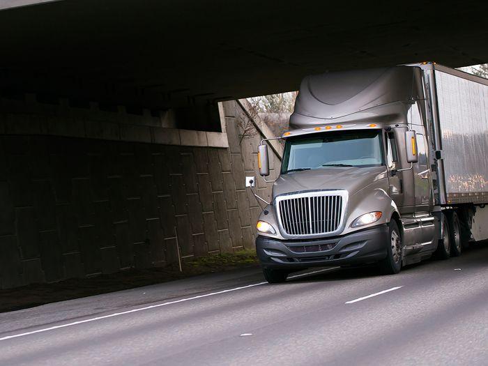 A modern semi-truck driving on an open highway.