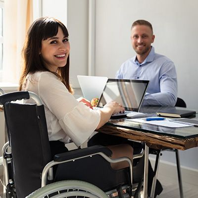 Happy Disabled Businesswoman Working On Laptop With Her Partner