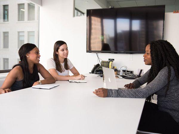 Three women in an office talking.