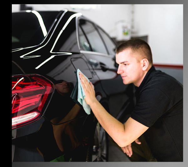 A detailer using a car detailing rag to wipe the hood of a luxury sedan.