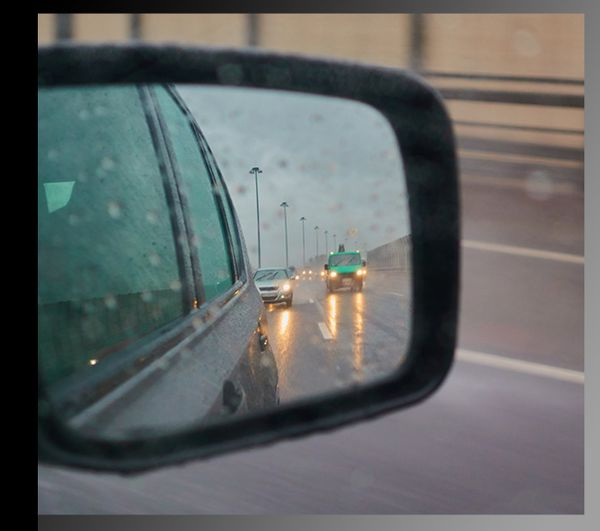 A close up shot of a car's side mirror, looking back at the road on a rainy day.