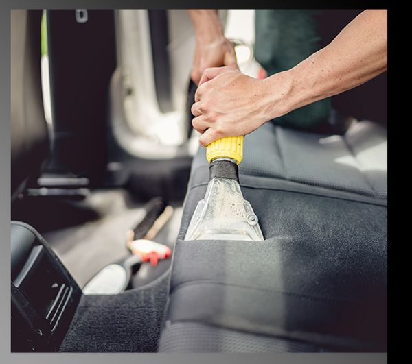 A car detailer using a vacuum to clean the back seats of a vehicle.