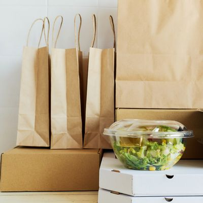 An image of salads and bags of takeout food.