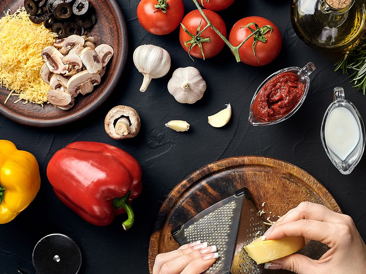 An image of a variety of fresh ingredients and a person grating cheese.
