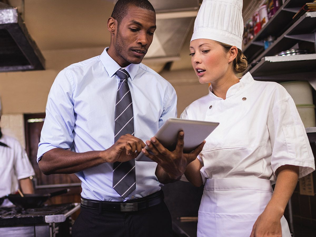 An image of a man with a notepad talking to a chef.