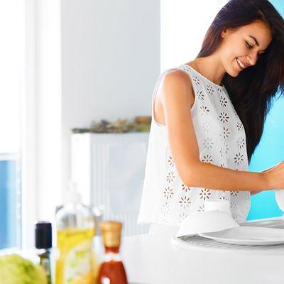An image of a woman washing a dish.