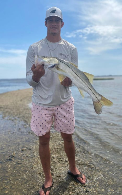man holding fish on shore