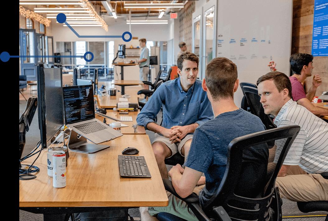 Men having discussion around computer workstation