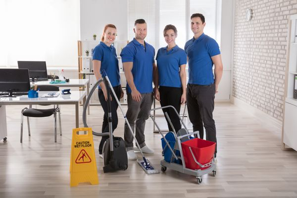 Team of cleaning technicians smiling for a photo