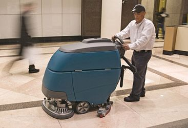 Technician pushing floor cleaning device