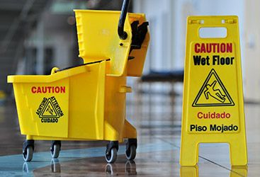 Commercial mopping bucket next to a wet floor sign