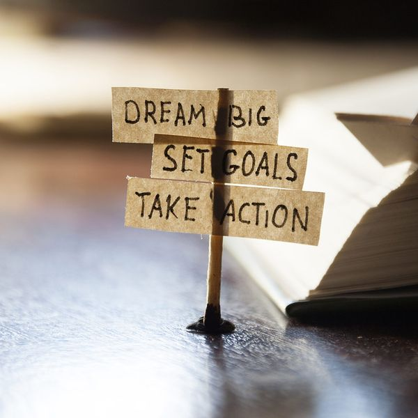 """image of a stick with notes on a desk that say """"dream big, set goals, take action."""""""