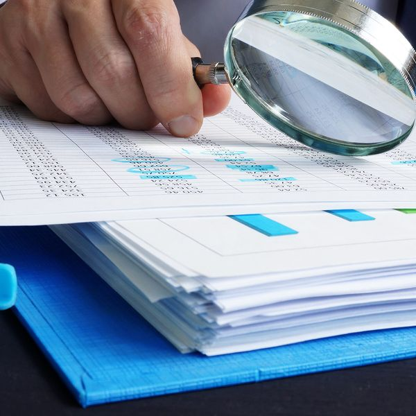 image of a person with a magnifying glass looking over budget reports and spending