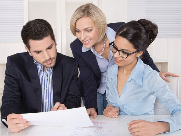 Image of 3 business people working together and looking at documents