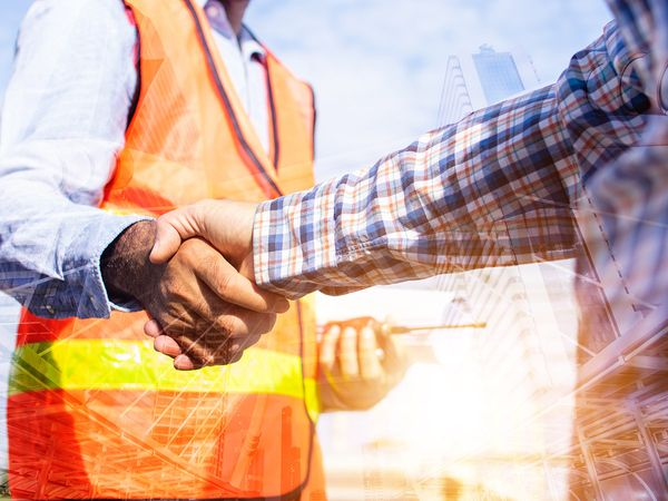 Architect contractor shaking hands with a client at a construction site
