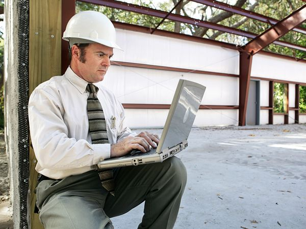 Businessman in a hardhat working on a laptop at the jobsite