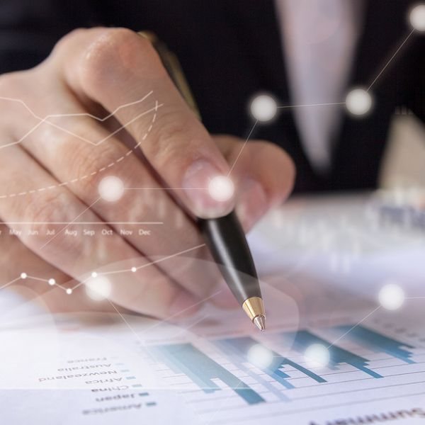 image of a man writing with a pen on a chart
