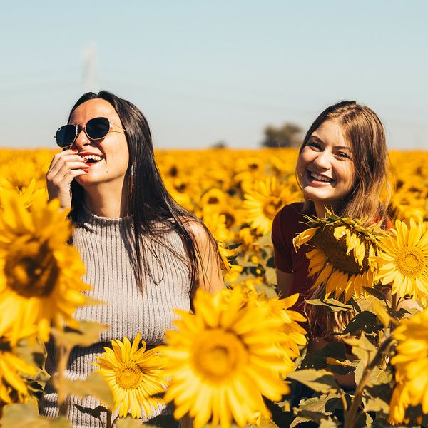 Young women laughing in sunflower field.