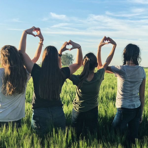 Young woman standing in a field creating heart shapes with their hands.