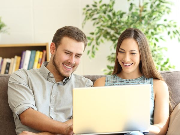 A young couple smiling at a surrogate's profile on their laptop.