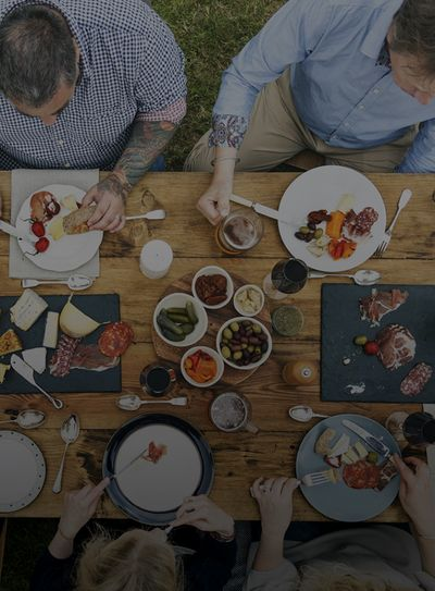 Friends enjoy eating together with custom charcuterie boards from Pompo's Boards.
