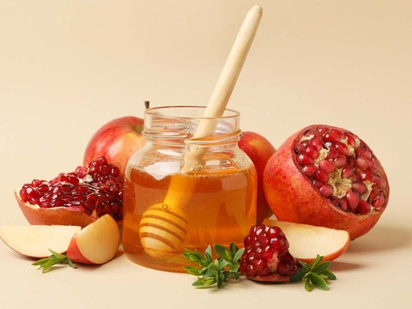 Apple, honey and pomegranate on beige background