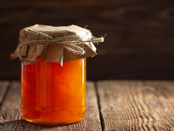 Jar with apricot jam on wooden table