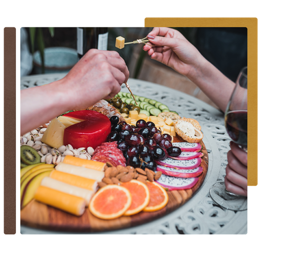 Beautiful fruits, meats, and cheese sit atop a charcuterie board from Pompo's Boards.