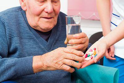 Image of a man taking his medication