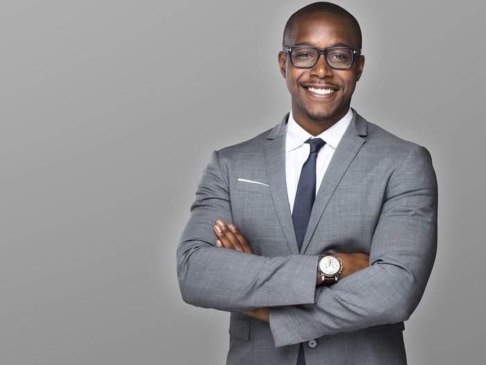 Businessman in a suit with a watch and glasses smiling.