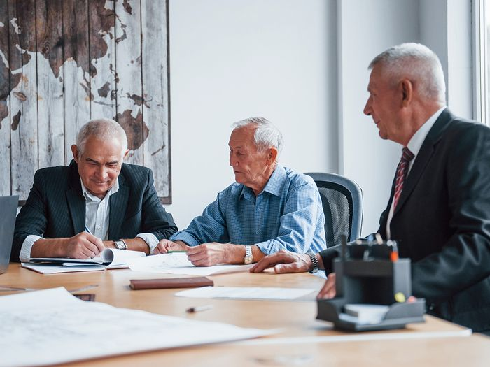 Three gentlemen in suits sitting at a boardroom table with paperwork in front of them.