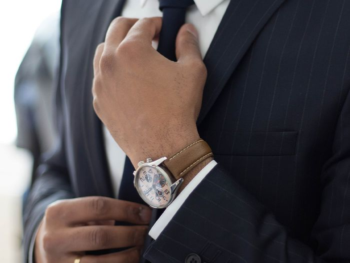 Person in a business suit adjusting their tie.