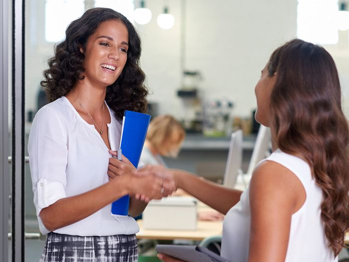 Two female coworkers smiling and shaking hands in a modern office.