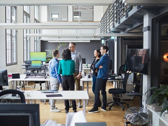 A group of young people standing in a circle talking in a modern office.