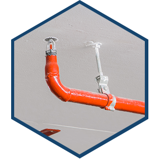 Fire sprinkler and orange pipe installed to a ceiling.