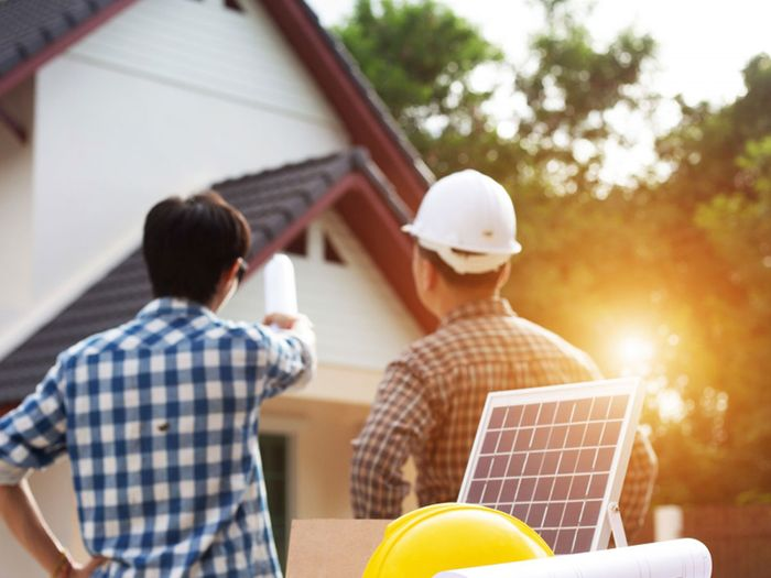 Two men standing in front of a house discussing solar panels.