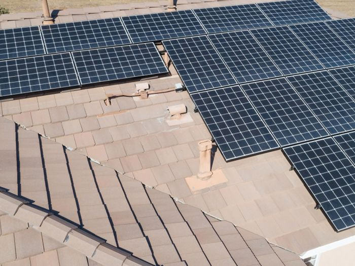 An aerial view of a roof lined with solar panels.