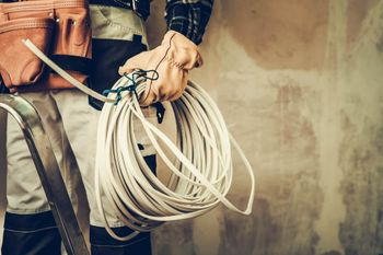 Image of a commercial electrician holding a wire.