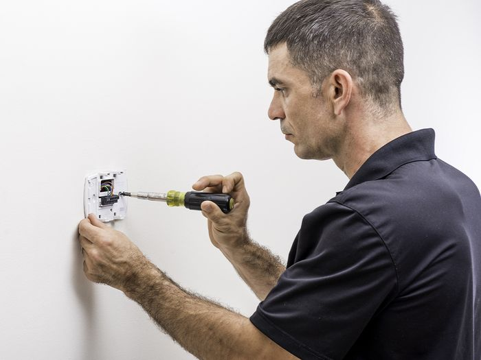 Image of an HVAC professional installing a thermostat.