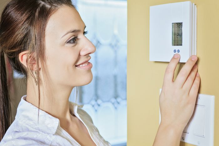 Image of a woman adjusting a thermostat.