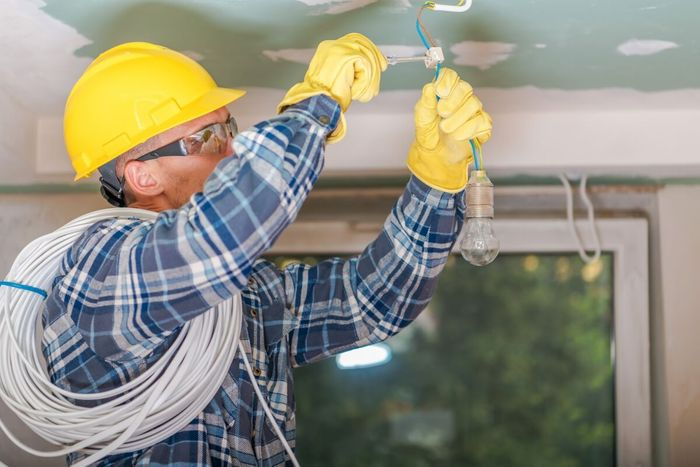 Image of a commercial electrician working a light socket.