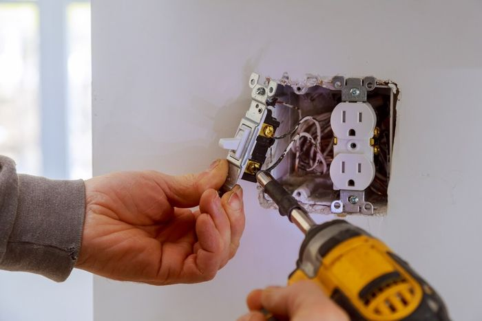 Image of a commercial electrician fixing an electrical outlet.