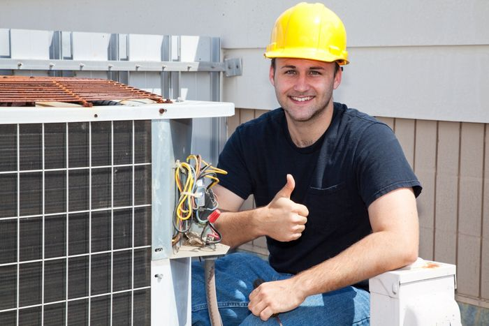 Image of an HVAC tech in front of a compressor.